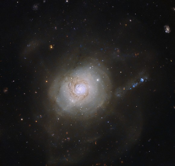 """Only rarely does an astronomical object have a political association. However, the spiral galaxy NGC 7252 acquired exactly that when it was given an unusual nickname. In December 1953, the US President Dwight D. Eisenhower gave a speech advocating the use of nuclear power for peaceful purposes. This """"Atoms for Peace"""" speech was significant for the scientific community, as it brought nuclear research into the public domain, and NGC 7252, which has a superficial resemblance to an atomic nucleus surrounded by the loops of electronic orbits, was dubbed the Atoms for Peace galaxy in honour of this. These loops are well visible in a wider field of view image. This nickname is quite ironic, as the galaxy's past was anything but peaceful. Its peculiar appearance is the result of a collision between two galaxies that took place about a billion years ago, which ripped both galaxies apart. The loop-like outer structures, likely made up of dust and stars flung outwards by the crash, but recalling orbiting electrons in an atom, are partly responsible for the galaxy's nickname. This NASA/ESA Hubble Space Telescope image shows the inner parts of the galaxy, revealing a pinwheel-shaped disc that is rotating in a direction opposite to the rest of the galaxy. This disc resembles a spiral galaxy like our own galaxy, the Milky Way, but is only about 10 000 light-years across — about a tenth of the size of the Milky Way. It is believed that this whirling structure is a remnant of the galactic collision. It will most likely have vanished in a few billion years' time, when NGC 7252 will have completed its merging process."""